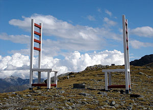 Timmelsjoch - Large chairs at the pass, one on each side of the Austria-Italy border with a border marker in between