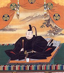 Painting of an mediaeval Asian man seated and dressed in splendour.