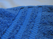 Close-up photo of a bath towel, made of terrycloth, showing the absorbing fibres, along with a decorative pattern.