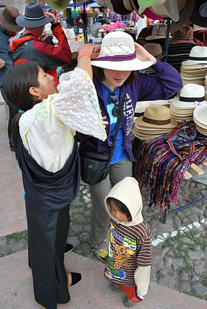 Otavalo (city) - An Otavaleña in traditional dress works with a customer in the open-air market in Otavalo