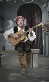 A modern-day troubadour (Owain Phyfe) plays for an audience at a Renaissance fair in 2003.