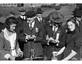Two women pouring cider from pitchers and two newspaper reporters taking notes, October 1920 (WASTATE 1484).jpeg