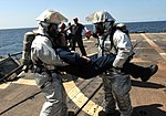 U.S. Navy Damage Controlman 2nd Class Nicholas Brown, left, and Counselor 1st Class Robert Ehrhart, right, carry a mock casualty during a drill on the flight deck of the guided missile frigate USS Underwood (FFG 120905-N-ZE938-032.jpg