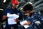 U.S. Navy Logistics Specialist 1st Class Rodway McCloggan, left, relays a message to Information Systems Technician 3rd Class Erica Dent during a damage control olympics competition June 10, 2013, aboard 130610-N-XE109-268.jpg