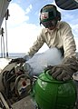 US Navy 031126-N-7871M-001 Carrier Airborne Early Warning Squadron One Two One (VAW-121) Aircrew Survival Equipmentman 3rd Class Bryan Ramirez of Long Beach, Calif., refills a liquid oxygen tank for an aircraft on the flight d.jpg