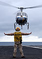 US Navy 040128-N-3241H-018 Chief Aviation Boatswain's Mate Glenn Harrison guides a commercial aerial filming helicopter safely to the flight deck aboard USS Carl Vinson (CVN 70).jpg
