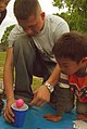 US Navy 070421-N-4124C-028 Gunner's Mate 3rd Class Eric Young, assigned to USS Juneau (LPD 10), helps Japanese children of the foster care facility Koyoryo Children's Home decorate an Easter egg as part of a visit.jpg