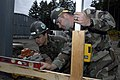 US Navy 070521-N-7157V-001 Steelworker 3rd Class Oscar Rabago, left, and Builder 2nd Class Adam Beardsley, assigned to Construction Battalion Maintenance Unit at Naval Base Kitsap, eye the level on a crossbeam of a warehouse co.jpg