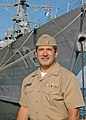 US Navy 070912-N-6611F-007 Cmdr. Frank Olmo, recipient of the Atlantic Fleet Vice Adm. James B. Stockdale Leadership Award, stands in front of his prior command ship, USS Mahan (DDG 72).jpg