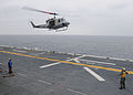 US Navy 100122-N-9950J-027 Aviation Boatswain's Mate (Handling) 3rd Class Patrick Neimeyer, from Montgomery, Ala., directs the landing of a UH-1N Huey helicopter aboard the forward-deployed amphibious assault ship USS Essex (LH.jpg