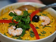 A bowl filled with creamy yellow paste, topped with shrimp and green herbs.