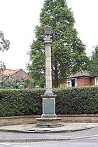 tall, thin gothic revival memorial.  A tall round pillar on a square base in a residential area, a bungalow discretely behind a hedge.  Behind the pillar is a neatly clipped hedge and a tall, green conifer.
