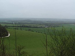 View of rolling agricultural fields and hedgerows under an overcast sky