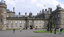 View of the Palace of Holyrood House showing the Royal Standard of Scotland flying from the rooftop flagpole, indicating that Her Majesty the Queen is not in residence.