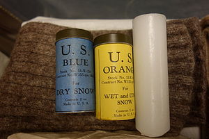 """Ski wax - Vintage ski waxes, once used by U.S. Army ski troops. Left to right are: grip waxes in canisters (blue for """"dry snow"""" and yellow for """"wet and corn snow"""") and a paraffin glide wax."""