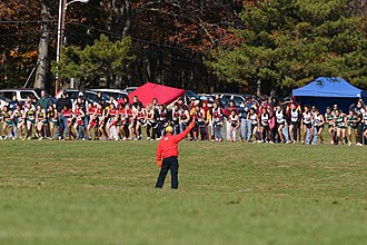 Cross country running - Start of a typical cross country race as official fires a gun to signal start.