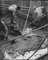 """Spreading mortar over the bedrock."" - NARA - 294149.tif"