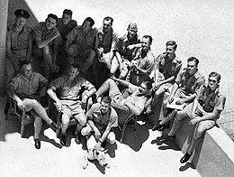 Informal high-angled portrait of fourteen men in light-coloured military shorts and shirts, with a dog in the foreground