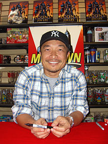 Lee seated at a table, smiling
