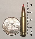 Photo of a 5.7×28mm SS196SR cartridge next to a quarter and ruler, in a size comparison.