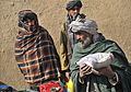A Molla Owrang village resident carries a bag of rice he received from Afghan National Police officers in Nawbahar district, Zabul province, Afghanistan, Feb 120207-N-UD522-078.jpg