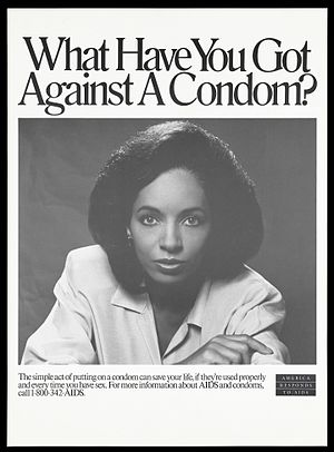 A poster promotes condom use. A black woman with one hand on her arm looks directly at Wellcome L0052333.jpg