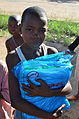 A girl collecting mosquito nets for her family, DR Congo, October 2012 (8406177038).jpg