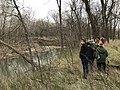 A group o fpeople gather by the creek's edge at Rock Creek Crossing in Council Grove, KS (9d7ad46e77c347fcaf0a688acec86215).JPG