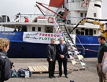"Two men in suits in front of a ship. The vessel is titled the Rachel Corrie and a banner reads ""Freedom Flotilla"""