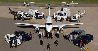 California Department of Justice - An aerial shot of California Department of Justice Special Agents posing with several CA DOJ vehicles and aircraft.