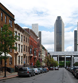 An urban street with cars parked along either side. On the left is a group of ornate three-story brick rowhouses in various colors. In the background is a tall modernist office tower, with smaller versions on its flanks.