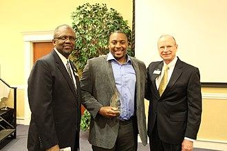 Nik Lewis - Lewis (center) accepting the Young Alumni Award at Southern Arkansas University