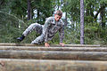 An Army Junior Officer Training Corps cadet navigates a log-hurdle obstacle located on the 7th Special Forces (Airborne) compound.jpg