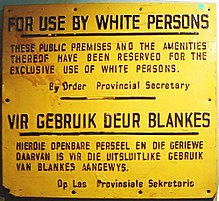 "A sign with text in English and Afrikaans. The English text reads: ""For Use By White Persons. These public premises and the amenities thereof have been reserved for the exclusive use of white persons. By Order Provincial Secretary""."