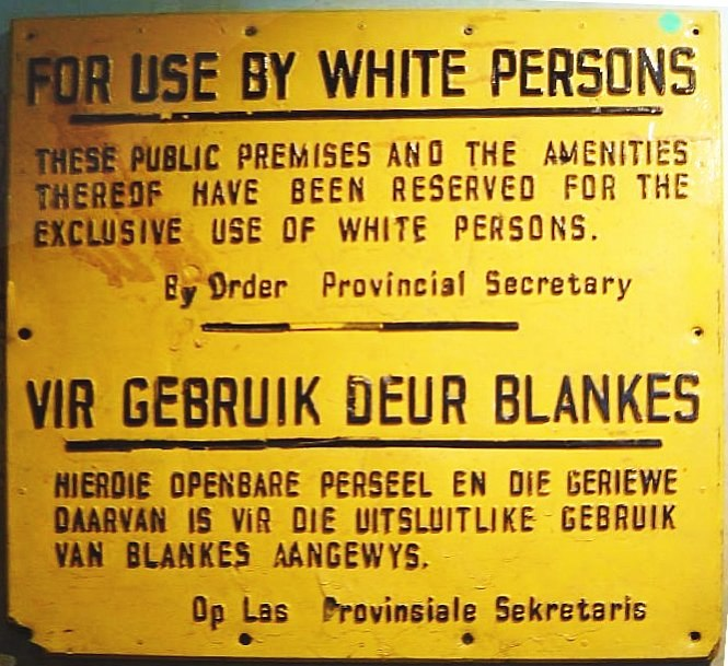 "A rectangular yellow wall plaque. It contains a message written in black in both English and Afrikaans. In English, the message reads: ""For Use by White Persons. These public premises and the amenities thereof have been reserved for the exclusive use of white persons. By Order Provincial Secretary""."