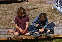 Arthur Rothstein, Boy building a model airplane as girl watches, FSA camp, Robstown, Texas, 1942.jpg