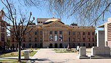 frontal view of the Arizona State Capitol, in winter, framed by the bare limbs of trees, showing the Arizona granite of the building topped by a copper dome