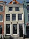 foto van Huis met geverfde lijstgevel. Dakkapel. Eenvoudige voordeuromlijsting; gebogen kalf; rozetbovenlicht. Hardstenen plint; hardstenen stoeptreden