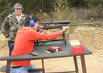 Benchrest shooting - Benchrest shooting with a Mauser rifle. This is an example of the non-competitive use of benchrest techniques. Neither the rifle, the rest, or the bench shown would be found in formal competition. They show, rather, adaptations of benchrest ideas for the more common hunting rifle.