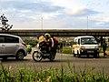 Boda boda motorist with loads and passenger on busy road.jpg