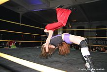A Caucasian female wrestler executes a throw that involves lifting her opponent up in the air and slamming the opponent's back inside a wrestling ring.
