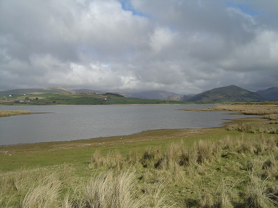A view of Broad Water with grass in the foreground leading down to the shore , and hills in the background behind the lake.