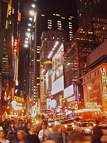 Photograph of a crowded city street at night. The street is in a commercial district; the buildings all have at least several stories, and some are high rise. The buildings have elaborate signs, many of which incorporate neon lighting. There are prominent signs for Madame Tussaud's, Loew's, Empire, AMC 25 Theatre, and Modell's.