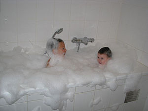 English: Two children enjoying a bubble bath
