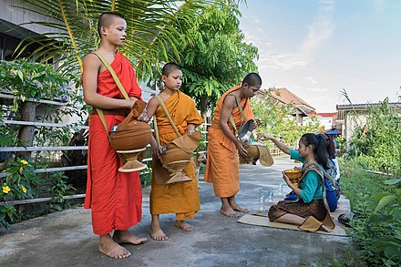 Buddhist monks collect alms in Si Phan Don, Laos. Giving is a key virtue in Buddhism. Buddhist alms in Si Phan Don.jpg