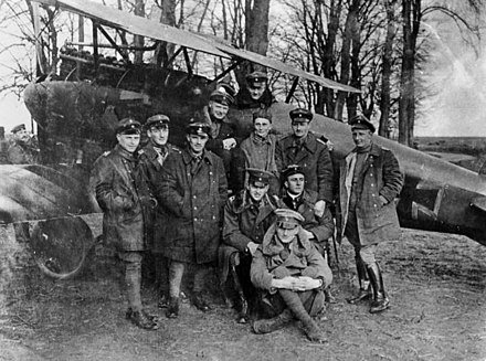 "Richthofen in the cockpit of his famous Rotes Flugzeug (""Red Aircraft"") with other members of Jasta 11, including his brother Lothar (sitting, front), 23 April 1917 Bundesarchiv Bild 183-2004-0430-501, Jagdstaffel 11, Manfred v. Richthofen.jpg"