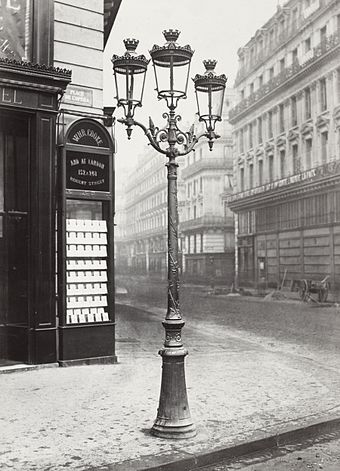 "In the 1860s, Paris streets and monuments were illuminated by 56,000 gas lamps, giving it the name ""The City of Light."" Charles Marville, Place de l'Opera, 1878.jpg"