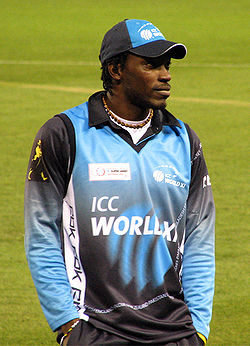 A man standing with his hands in his pockets. He is wearing a blue–black hat and top