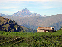 Small stone house, with mountains in background