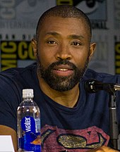 A photograph of Cress Williams speaking at a convention behind a microphone